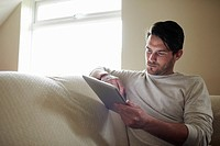 Young man on sofa using digital tablet
