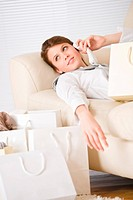 Young businesswoman with shopping bag on sofa