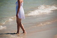 young female, very feminine in summer dress on the sandy beach, subtle symbol of summer leisure