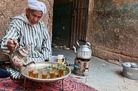 traditional Berber grandfather pouring tea in the Southern Atlas Mountains, Morocco