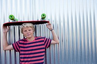 Teenage boy holding a longboard on his head