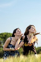 Couple of girls playing and enjoyment whit flowers in the countryside