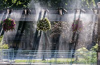 Sunlight streams through floral baskets hanging from an arbor on a patio, Ontario, Canada  A sprinkler system creates a surreal back-lit effect as wat...