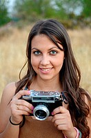Cute young woman using an old camera