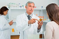 Pharmacist pointing at a flask of pills in front of a customer in a pharmacy