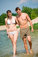Happy couple in swimwear walk in lake