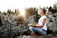 A beautiful young woman meditating on a cliff at sunset in Montana.