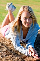 Sportive young woman relax on hay bales