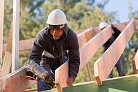 Carpenter nailing a roof rafter