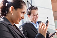 Business couple in office looking at tablet and smartphone