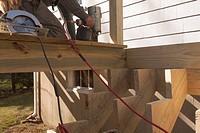 Hispanic carpenter nailing decking at stair stringers