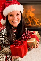 Christmas present woman Santa hat home fireplace
