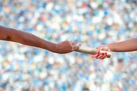 Relay athletes passing a baton, close up