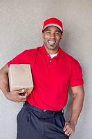 Portrait of a happy young man holding delivery box against wall