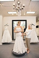 Beautiful woman dressed up as bride with senior employee helping in bridal store