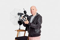 Portrait of happy senior man with camera standing in photographer´s studio