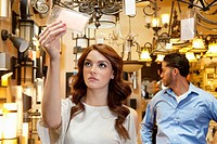 Beautiful young woman looking at price tag with man browsing in background
