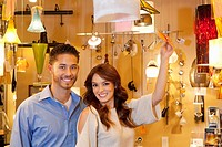 Portrait of young couple with price tag in lights store