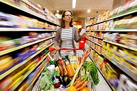 Woman pushing a full shopping cart through a corridor of the food section while shopping in a self-service grocery department, supermarket, Germany, E...