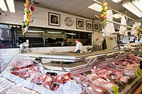 Butcher working in behind with huge amount of meat displayed in case