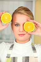 Woman holding orange halves to her face