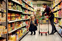 Young couple grocery shopping at the supermarket, shelves with various products, food hall, supermarket, Germany, Europe