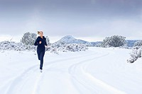 Hispanic woman jogging on snow covered road