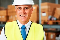 Smiling warehouse worker wearing a hardhat in the factory