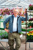 Portrait of smiling mature caucasian male florist leaning on tray of flowers in nursery