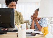Black mother and son using laptop together