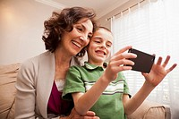 Caucasian grandmother and grandson looking at cell phone