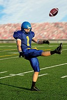Caucasian football player kicking football