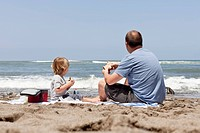 Caucasian father and son eating on beach