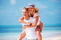 Portrait of mature man giving piggyback ride to woman on beach
