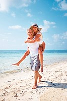 Full length of happy mature couple enjoying while piggyback ride on beach