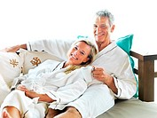 Portrait of happy mature couple lying together on bed in hotel room