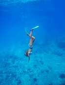Young woman diving deep underwater with snorkeling gear_ copyspace