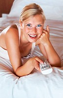 Smiling young girl watching tv lying on the bed at home