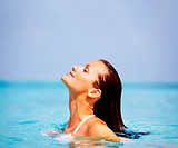 Attractive young woman enjoying swimming in cool refreshing sea water