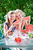Two sisters eating watermelon in the garden