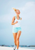 Portrait of healthy young woman jogging on beach