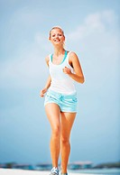 Portrait of health conscious woman jogging at beach