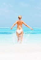 Rear view of woman in bikini walking in water at beach