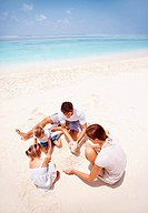 Young family sitting building sand castles on the beach