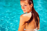 Beautiful woman looking sensual while standing in the pool