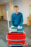 Male cleaner pushing trolley with cleaning equipment
