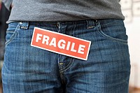 Midsection view of a person with a word 'Fragile' stuck on its jeans (thumbnail)
