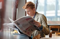 Man sitting in a restaurant and reading a newspaper (thumbnail)