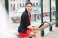 Woman sitting at a bus stop
