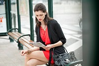 Woman sitting at bus stop and reading a newspaper